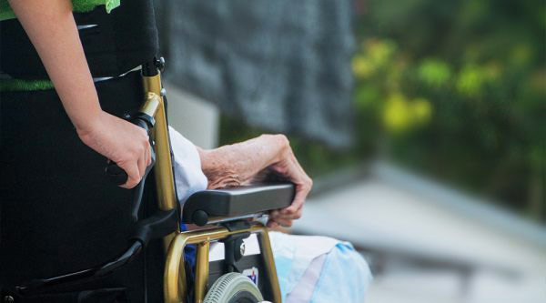 home carer with elderly woman in wheelchair